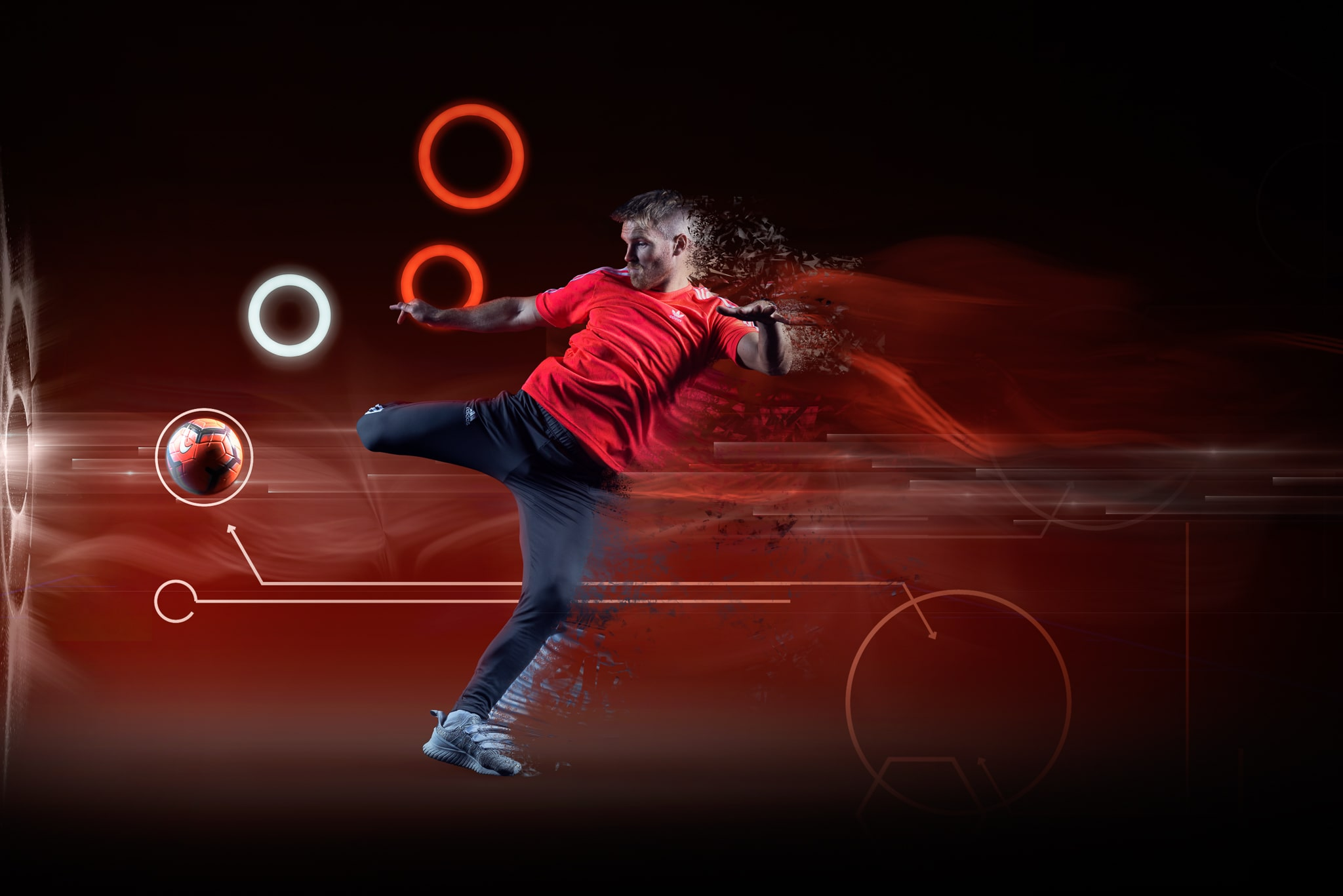 Footballer kicking football on Red Background